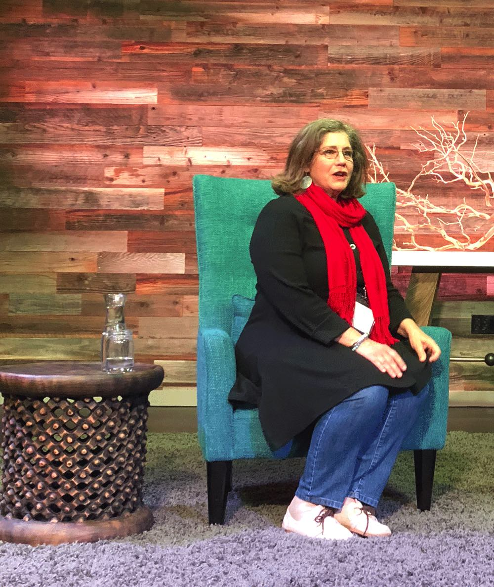 Sharon Silver sitting on stage speaking about supporting parent-employees in corporations at a live event.