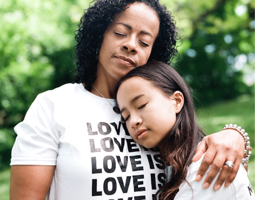 African-American mom empathizing as she resolves an argument with Asian tween wearing a love t-shirt.